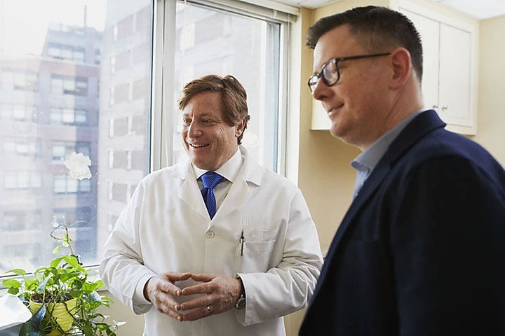 Doctor in lab coat having a discussion with a man in a suit