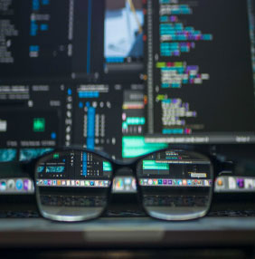 Glasses in front of a computer monitor with code